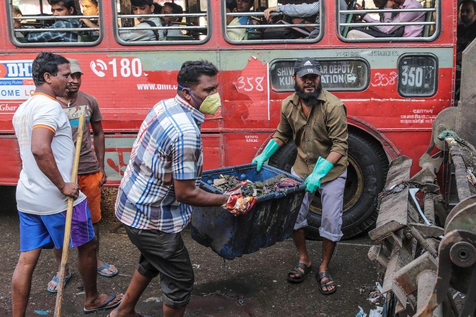 Municipal Corporation of Greater Mumbai (MCGM) workers clear roadside garbage near the Deonar landfill site in Mumbai, India,
