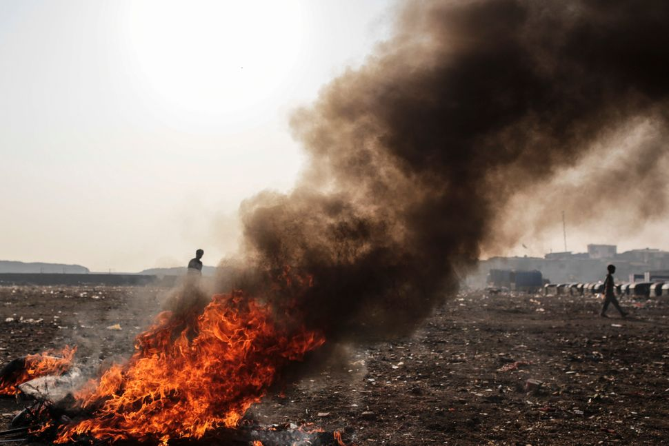 Smoke billows from a fire burning electronic waste near the Deonar landfill site in Mumbai, India, on Wednesday, March 11, 20