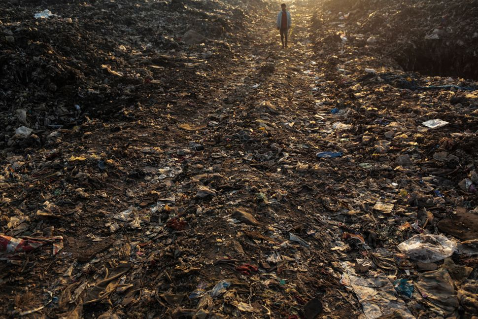 A rag picker walks though garbage at the Deonar landfill site in Mumbai, India, on Wednesday, March 11, 2015.