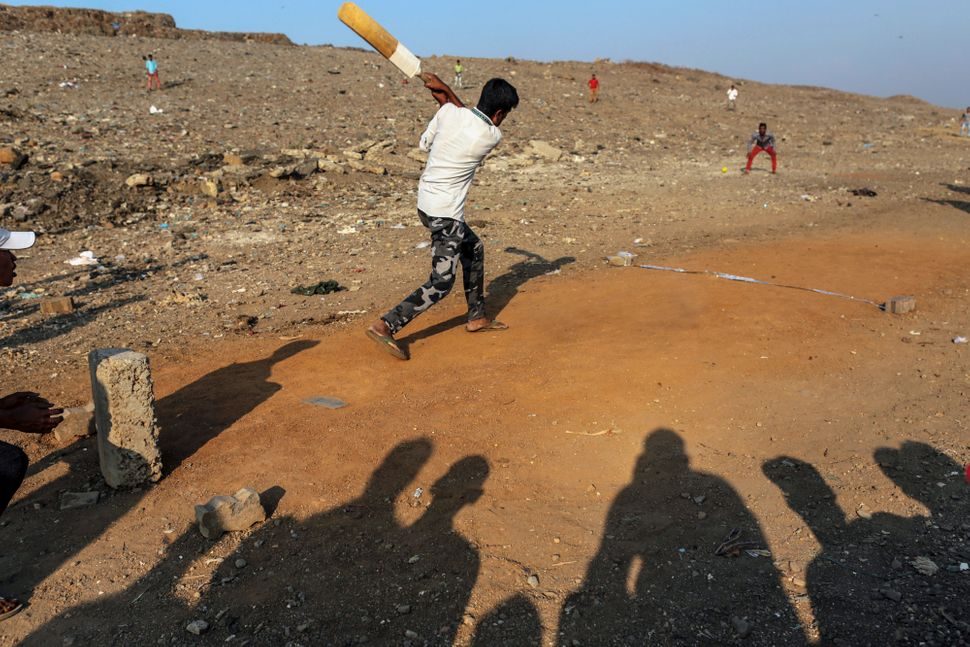 Boys play a game of cricket at the Deonar landfill site in Mumbai, India, on Wednesday, March 11, 2015.