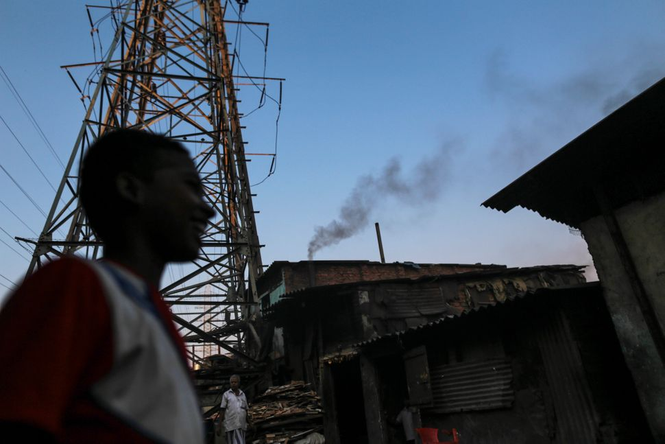 Smoke billows from a factory chimney at a slum in the Govandi area of  Mumbai, India, on Wednesday, March 11, 2015.