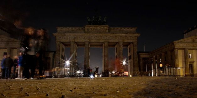 People gather around the Brandenburg Gate after the lights were turned off to mark Earth Hour in Berlin, Saturday, March 29,