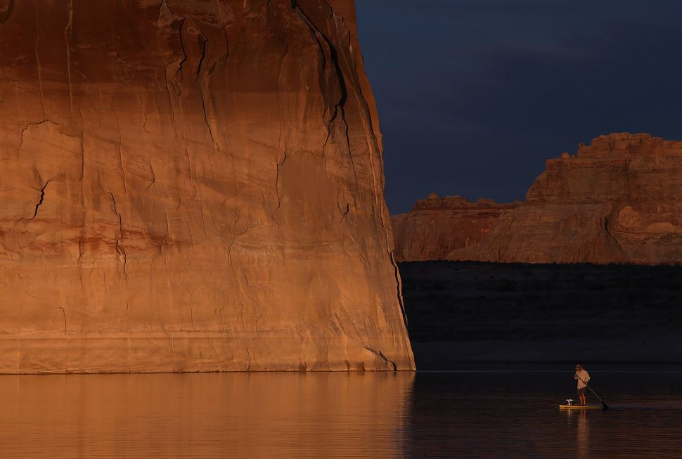 A paddleboarder floats by Lone rock on Lake Powell on March 29, 2015 near Big Water, Utah.