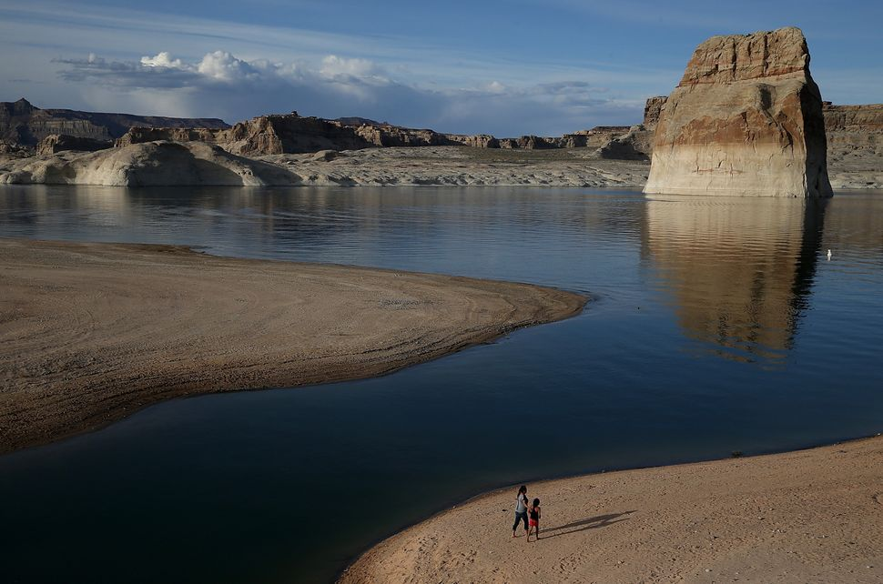 People walk on a beach that used to be the bottom of Lake Powell at Lone Rock Camp on March 29, 2015 near Big Water, Utah.