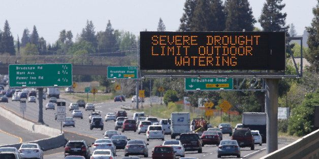 Motorists pass a sign, Thursday, April 2, 2015, in Rancho Cordova, Calif., reminding them to reduce water use due to the stat