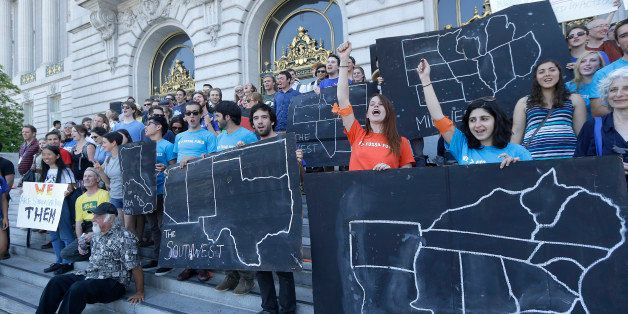 College students and supporters hold up signs at a rally to support fossil fuel divestment outside of City Hall in San Franci