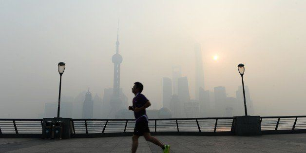This photo taken on November 12, 2014 shows a resident exercising amid heavy smog on the Bund in Shanghai as the local meteor