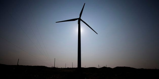 A wind turbine manufactured by DeWind Co. is silhouetted against the sun as it stands at a wind farm operated by EcoPower Co.