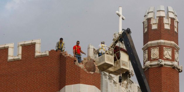FILE - In this Nov. 6, 2011 file photo, maintenance workers inspect the damage to one of the spires on Benedictine Hall at St