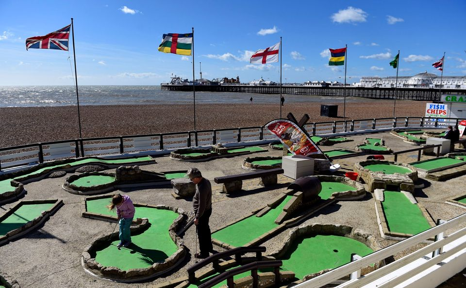 Members of the public play a game of crazy golf on Brighton beach, as fierce winds battered Britain, with road and rail trave