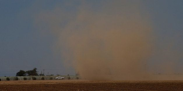 MADERA, CA - APRIL 24:  A dust devil kicks up dirt as it forms over an empty field on April 24, 2015 in Madera, California. A