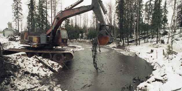 Heavy machinery is used to scoop up oily debris from the water s of a tributary of the Kolva River, some 27 miles north of th