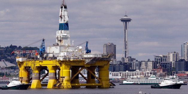 The oil drilling rig Polar Pioneer is towed toward a dock and in view of the Space Needle Thursday, May 14, 2015, in Elliott