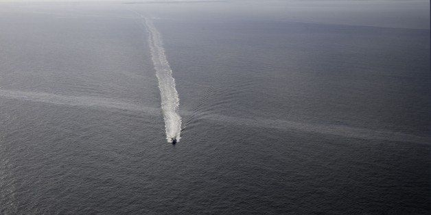 In this March 31, 2015 photo, a supply vessel crosses an oil sheen drifting from the site of the former Taylor Energy oil rig