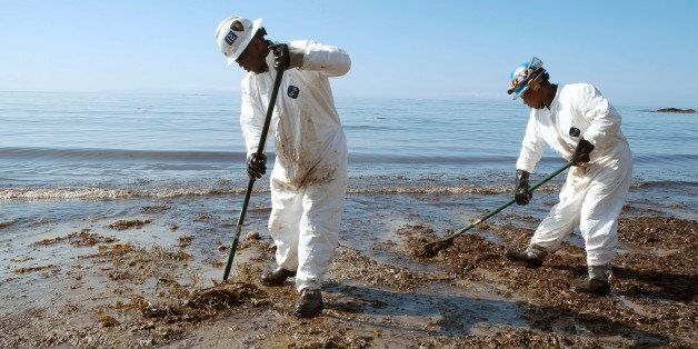 Crews from Patriot Environmental Services collect oil-covered seaweed and sand from the shoreline at Refugio State Beach, nor