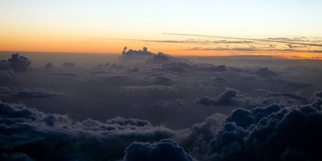 Sunset over the clouds pictured from a plane between Martinique and the Guadeloupe French Islands on May 9, 2015. AFP PHOTO/