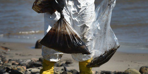 Workers clean oil from the rocks and beach at Refugio State Beach in Goleta, California, May 22, 2015. The oil company behind