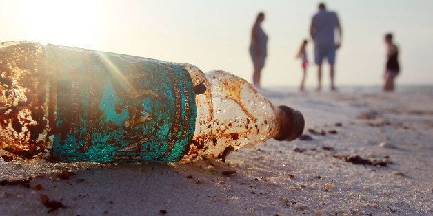 PENSACOLA, FL - JUNE 06:  A plastic bottle is seen coated in oil on Pensacola Beach as oil makes its way on shore from the De