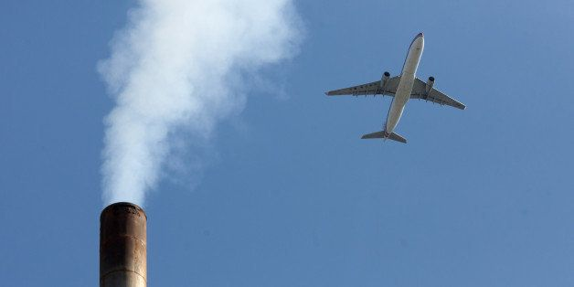 An aircraft flies past a smoke-stack in Beijing on May 30, 2012.   According to government sources, China is to set aside aro