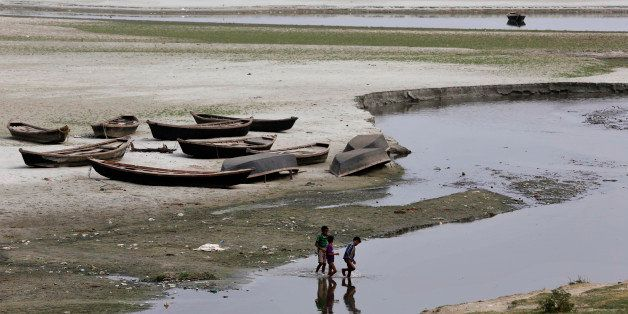 Indian children play near parked boats on the banks of river Ganges where water level has dried up in the summer in Allahabad