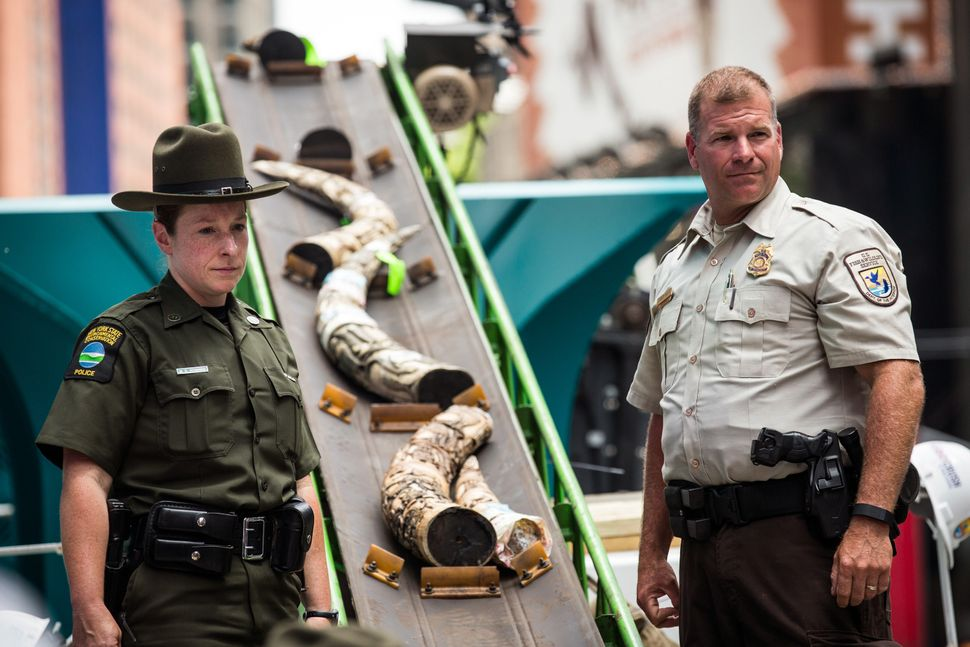Officials from the U.S. Fish and Wildlife Service destroy ivory trinkets confiscated by law enforcement in Times Square.