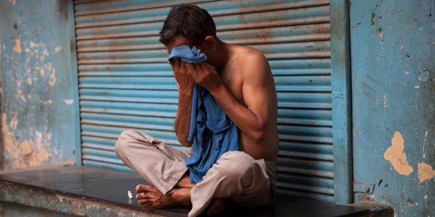 An Indian man wipes sweat off his face on a hot summer day in New Delhi, India, Sunday, May 24, 2015. Heat wave has tightened
