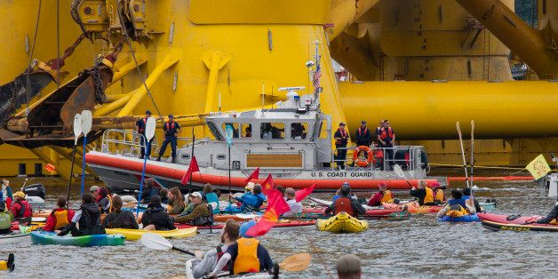 SEATTLE, WA - MAY 16:  A U.S. Coast Guard vessel keeps watch over ShellNo flotilla participants as they float in front of the