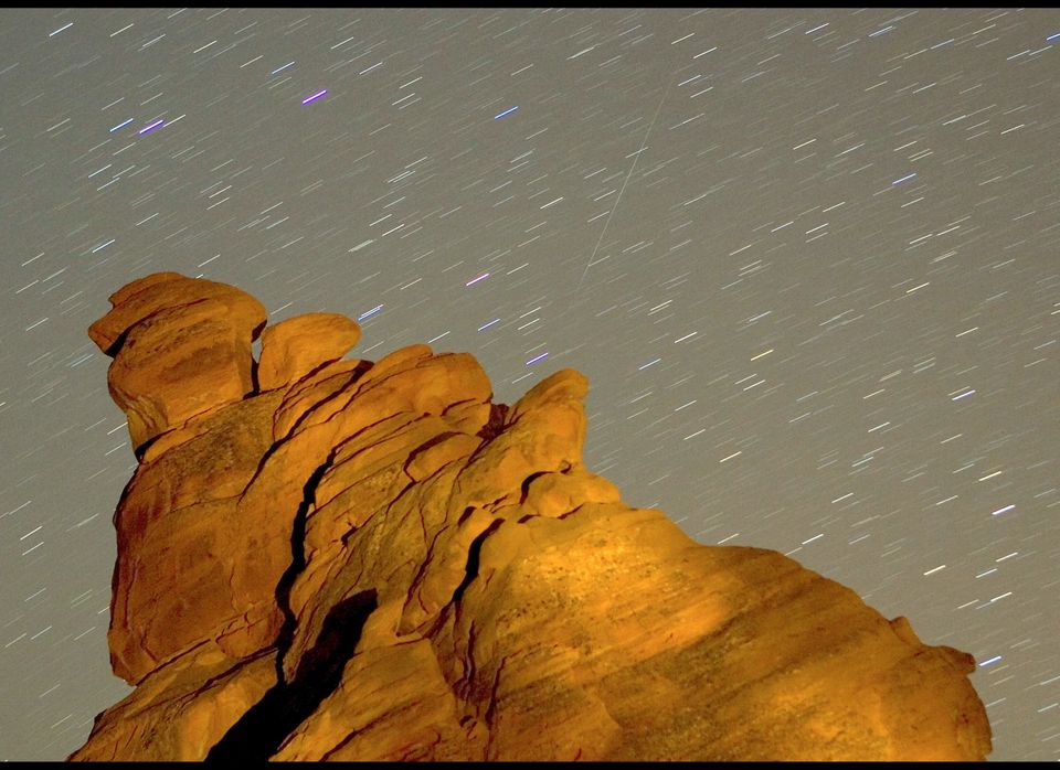 VALLEY OF FIRE STATE PARK, NV - DECEMBER 14: A Geminid meteor streaks diagonally across the sky against a field of star trail