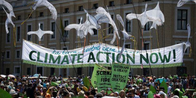 People hold a banner reading ' Climate action Now ' in St. Peter's Square, at the Vatican, Sunday, June 28, 2015. Greeting pe