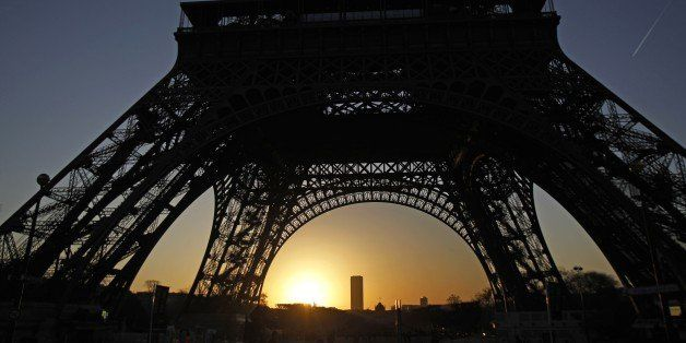 The sun rises behind the Eiffel Tower in Paris, Saturday, Jan. 14, 2012. (AP Photo/Michel Euler)