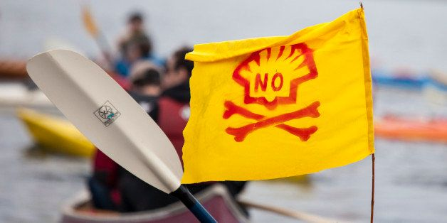 SEATTLE, WA - MAY 16:  A ShellNo flotilla participant paddles in a kayak with an anti-Shell flag during demonstrations agains