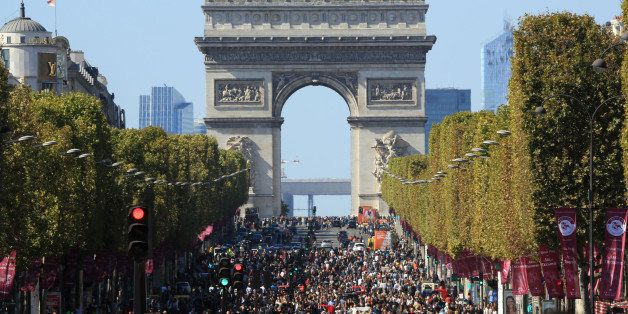 "People walk on the Champs Elysees during the ""day without cars"", in Paris, France, Sunday, Sept. 27, 2015. Pretty but noisy P"
