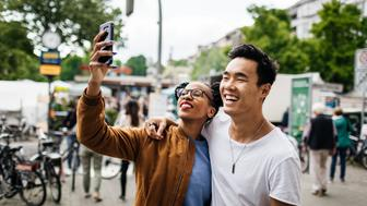 A young tourist couple standing in a new city take a photo of themselves using a smartphone.