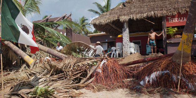 MELAQUE, MEXICO - OCTOBER 24: Workers clean out the 'Terrza Cortes' restaurant after damage from Hurricane Patricia October 2