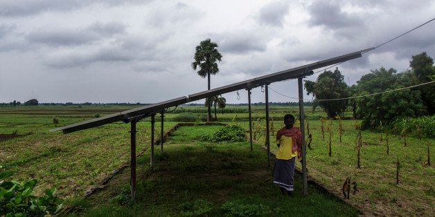 A man stands under solar panels, part of a solar power microgrid owned and operated by Veddis Solars Pvt., in the village of