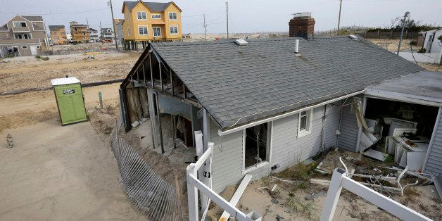 A home sits in ruins near others still being rebuilt on the second anniversary of Superstorm Sandy Wednesday, Oct. 29, 2014,