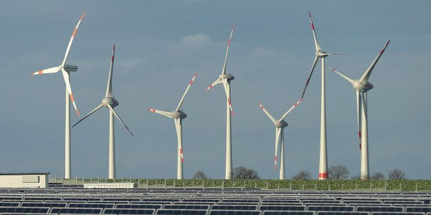 WERDER, GERMANY - OCTOBER 30:  Wind turbines stand behind a solar power park on October 30, 2013 near Werder, Germany. The Ge