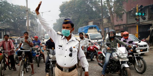 A traffic policeman wears a mask and controls traffic on a busy road in Mumbai, India, Tuesday, April 14, 2015. Air pollution
