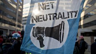 A demonstrator opposed to the roll back of net neutrality rules holds a sign outside the Federal Communications Commission (FCC) headquarters ahead of a open commission meeting in Washington, D.C., U.S., on Thursday, Dec. 14, 2017. The FCC is slated to vote to roll back a 2015 utility-style classification of broadband and a raft of related net neutrality rules, including bans on broadband providers blocking and slowing lawful internet traffic on its way to consumers. Photographer: Andrew Harrer/Bloomberg via Getty Images