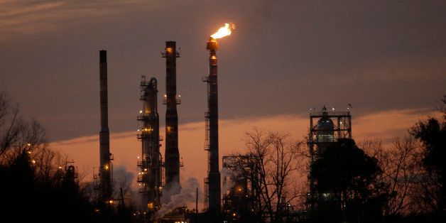 Stacks and burn-off from the Exxon Mobil refinery are seen at dusk in St. Bernard Parish, La., Friday, Feb. 13, 2015. (AP Pho