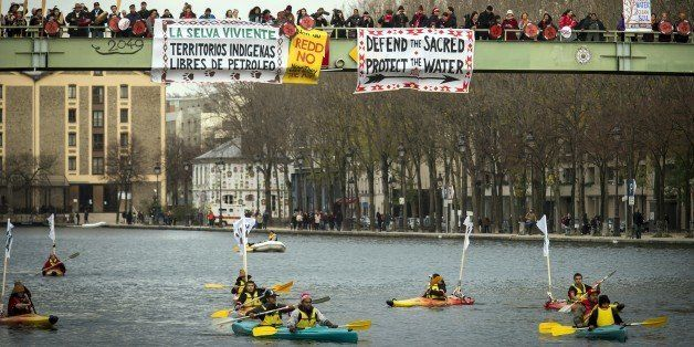 Indigenous people from South America paddle on kayaks as others stand on a bridge holding banners reading 'Native territories