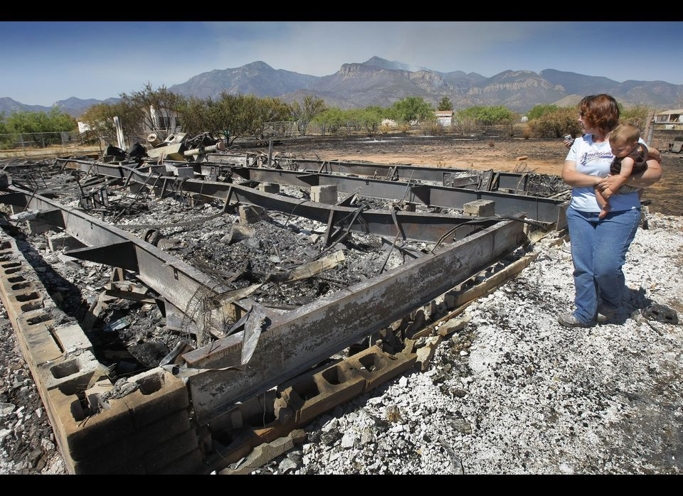 Gayle Gehr along with grandson Nathan Jacob look at their burned home  that was destroyed from the Monument Fire near Sierra