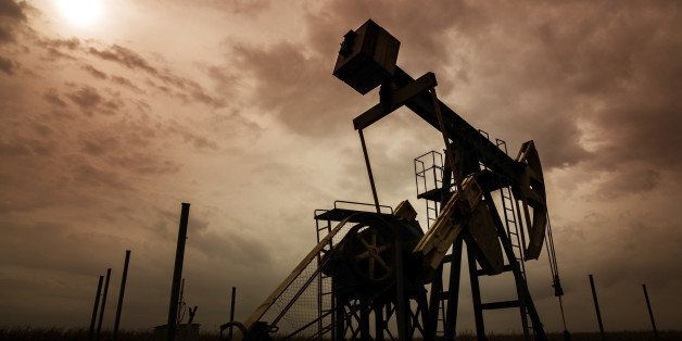 Operating oil and gas well silhouette in remote rural area, profiled on dramatic sky