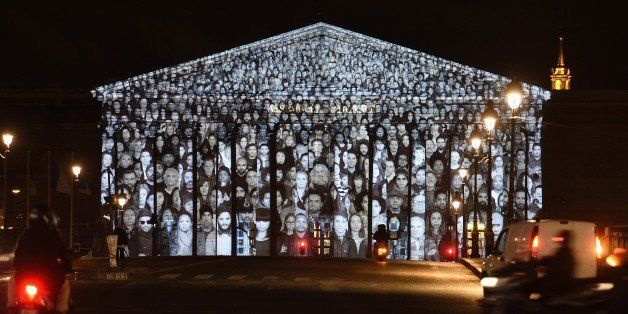 A picture taken on November 30, 2015 shows images of more than 500 people being projected onto the facade of the French Natio