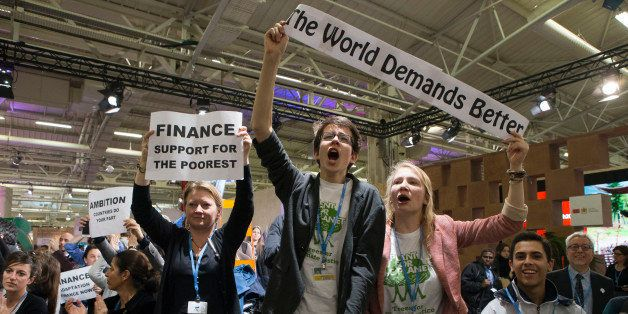NGO representatives and participants stage a sit-in protest closed to the plenary session to denounce the first draft COP21 C