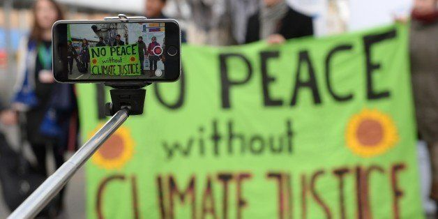 A person records with a selfie-stick a demonstration of activists of environmental organization Greenpeace at the venue of th