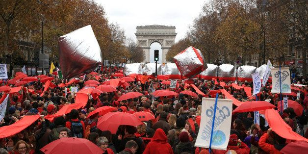 Climate activists demonstrate with red umbrellas in Paris, Saturday, Dec.12, 2015 during the COP21, the United Nations Climat