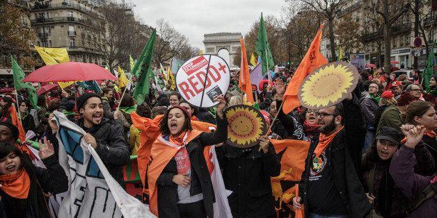 PARIS, FRANCE - DECEMBER 12: Activist shout during a demonstration near the Arc de Triomphe at the Avenue de la Grande Armee