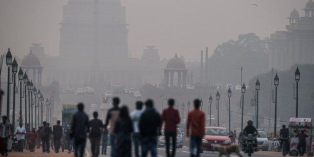 Indian pedestrians walk near smog enveloped government offices on Rajpath in New Delhi on December 1, 2015.  India's capital,