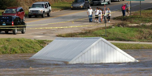 A building is submerged by the Pea river as people wait to cross in to downtown on highway 84 bridge, Dec. 26, 2015 in Elba,